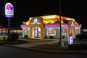 No one even noticed the flames next to this neon club known as Taco Bell.
